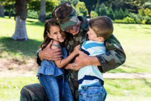 Military father hugging two children